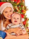 Mom wearing Santa hat holding  baby  under Stock Photography