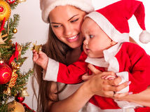 Mom wearing Santa hat holding  baby  under Stock Photo