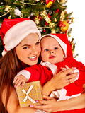 Mom wearing Santa hat holding  baby  under Stock Image