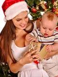 Mom wearing Santa hat holding  kid  under Royalty Free Stock Image