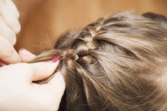 Mom weaves braids daughter at home Royalty Free Stock Image