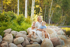 Mom in a white dress with her son and daughter sitting on large. Rocks on the lake in the summer and laughing stock photography