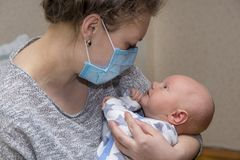 Mom, who is ill, keeps her baby in a protective medical mask Royalty Free Stock Photos