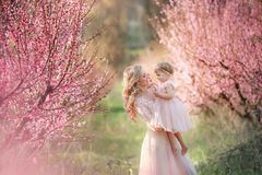 Free Mom With An Infant In The Rose Garden With Flowers Trees Stock Photos - 140735653