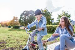 Free Mom Woman Teaches Riding Bike, Little Boy Son 3-5 Years Old, Training Rides, In Summer City, In Autumn In Park, Casual Royalty Free Stock Photo - 165477975