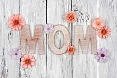 MOM wooden letters with paper flowers against white wood Royalty Free Stock Image