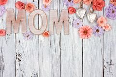 MOM wooden letters with top border of flowers against white wood Royalty Free Stock Image