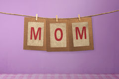 Mom word shape hanging with clothespin Stock Image