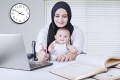 Mom Working while Holds her Baby Stock Photo