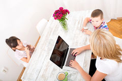 Mom working at home. A mother working at home with a laptop and parenting her two children Stock Image