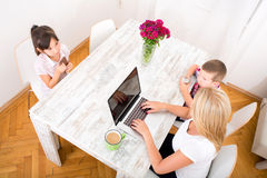 Mom working at home. A mother working at home with a laptop and parenting her two children Stock Photo