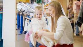 Mom wraps the doll for my daughter. A young mother wraps a new doll for her little daughter in a children`s store Royalty Free Stock Image