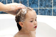Mom& x27;s hands washing little girly& x27;s head in the bathroom. The sym Stock Image