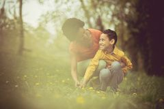 Mom, you are beautiful like this flower. Mother and son in the park stock photos