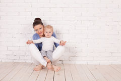 Mom and young boy sitting on the floor. Near the brick wall Royalty Free Stock Photos