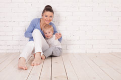 Mom and young boy sitting on the floor. Near the brick wall Royalty Free Stock Images