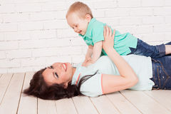 Mom and young boy son lying on the wooden floor play. 1 Stock Photo