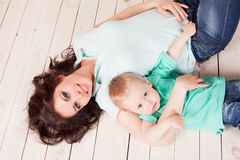 Mom and young boy son lying on the wooden floor. Play Stock Photo
