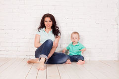 Mom and young boy son sit on the floor brick wall. Mom and young boy son sit on the floor white brick wall Stock Photo