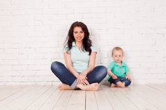 Mom and young boy son sit on the floor brick wall. Mom and young boy son sit on the floor white brick wall Royalty Free Stock Images