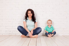Mom and young boy son sit on the floor brick wall. Mom and young boy son sit on the floor white brick wall Royalty Free Stock Photo