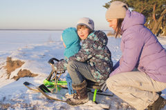 Mom and young children sledding down the hills. Royalty Free Stock Photography