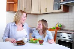 Mom and young daughter. Eating breakfast together in the kitchen Royalty Free Stock Images