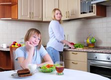 Mom and young daughter. Eating breakfast together in the kitchen Royalty Free Stock Photography