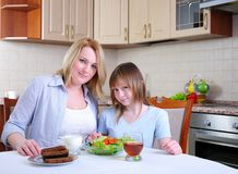 Mom and young daughter. Eating breakfast together in the kitchen Royalty Free Stock Image