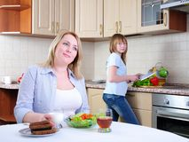 Mom and young daughter. Eating breakfast together in the kitchen Stock Image