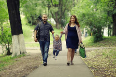 Mom and young daughter and dad  walking in summer park Stock Photo