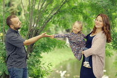 Mom and young daughter and dad  walking in summer park Royalty Free Stock Image