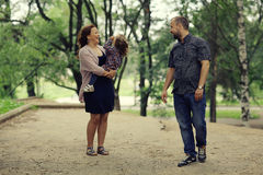 Mom and young daughter and dad  walking in summer park Stock Photos