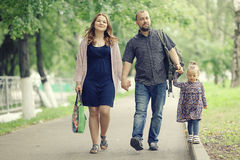 Mom and young daughter and dad walking in summer park royalty free stock images