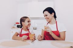 Mom and Young Girl Drinking Sweet Juice Together. stock photography