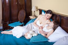 Mom and young girl lie in bed in the morning, hugging , smiling Stock Photos