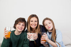 Mom with your two sons drinking juice in the breakfast Stock Image