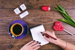 Moman übergibt Schreibensgrüße Rosa Tulip Flower, Lutscher, der Datumskalenderblock und zwei cendels auf rustikaler Tabelle für Lizenzfreies Stockbild