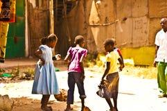 MOMBASSA,肯尼亚 2011年12月18日:一个小组在多灰尘的街道上的肯尼亚儿童游戏 免版税库存图片