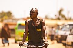 MOMBASSA,肯尼亚 2011年12月18日:一个肯尼亚人通过Mombassa街道骑他的推挤自行车 免版税库存照片