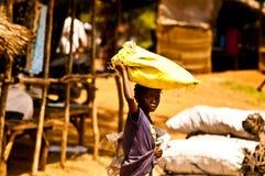 MOMBASSA,肯尼亚 2011年12月18日:肯尼亚女孩运载袋子在她的头的米 免版税库存照片