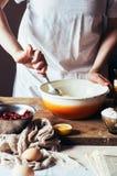 Moment av danande som lagar mat den sandiga kakan med körsbärsröd fyllning: blandning Arkivfoto