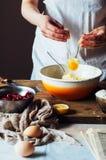 Moment av danande som lagar mat den sandiga kakan med körsbärsröd fyllning: blandning Royaltyfri Bild