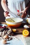 Moment av danande som lagar mat den sandiga kakan med körsbärsröd fyllning: blandning Arkivbilder