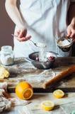 Moment av danande som lagar mat den sandiga kakan med körsbärsröd fyllning: blandning Arkivfoton