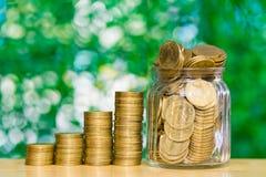 Moment av myntbuntar och pengar för guld- mynt i den glass kruset på flik Royaltyfri Bild