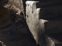 Moment av stentrappuppgången tände vid strålarna av solen mot en mörk väggbakgrund, abstrakt begrepptexturbakgrund Royaltyfri Bild