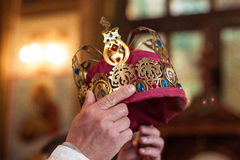 Moment of coronation. Crown in the hands of the pastor at the time of the coronation Stock Photography