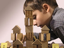 The moment of creation. The toy wooden castle and the boy keen on building Royalty Free Stock Image