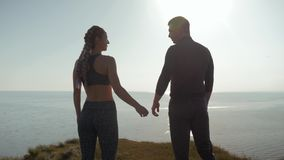 Moment d'harmonie, couple affectueux sportif tenant des mains observant le coucher du soleil à la position de l'eau sur la montag banque de vidéos